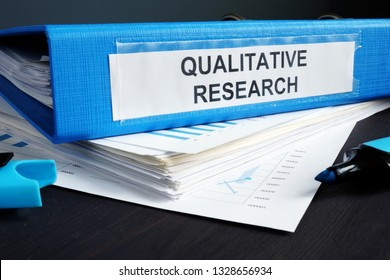 Qualitative research methods report in a blue folder.