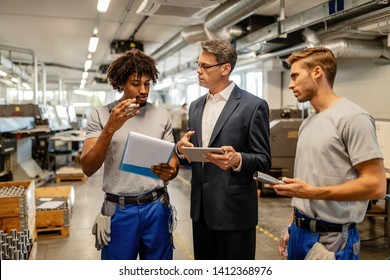 Quality control inspector and metal processing plant worker discussing while going through paperwork and using touchpad in a factory.
