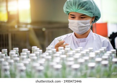 Quality control woman and manager wearing a lab coat to checking juice industrial process at factory. Teamwork at production line successful concept.