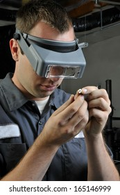 Quality Inspector wearing magnifying glasses inspecting a small manufactured part
