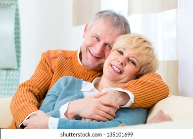 Quality of life - two elderly people sitting at home on the couch, he embraces his wife