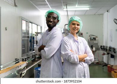 A quality supervisor or a food technician is inside the juice chamber. Employees are happy to work within an industrial facility. Male and female officers dressed in white and wearing hats