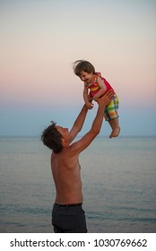 Quality time concept. Young father having fun and throwing her daughter in the air at sunset. Summer vacation at sea