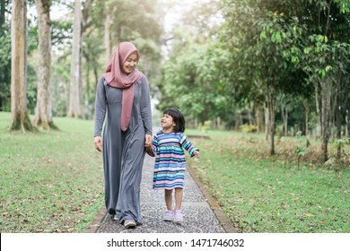 quality time veiled mother with little daughter go to park, muslim family