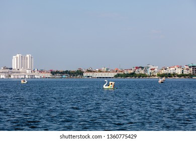 Quan Tay Ho or Westlake district in Hanoi. Lake Tay with swan paddle boats with city view on the background. Vietnam.