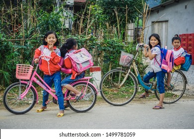 Quang Binh Province, Vietnam - January 26, 2018: Vietnamese children ride bicycles home after school.