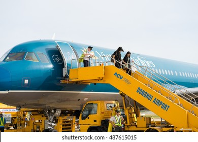 Quang Binh, Vietnam - June 16, 2016: Passengers going down with stairs from airplane just landed at Dong Hoi airport