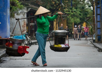 Quang Nam, Vietnam - MAY 2018: Stock image of a Vietnamese woman with conical hat carries a yoke on her shoulder along the street. Women with conical hat selling street food in the morning in market
