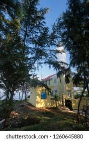 Quang Ngai, Vietnam - 2018: View of a lighthouse behind trees at Dung Quat beach