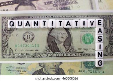 Quantitative Easing written on white cube with dollars background for QE concept.