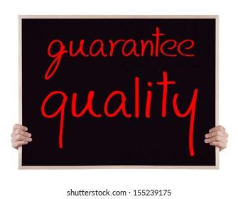 quarantee quality on blackboard with hands
