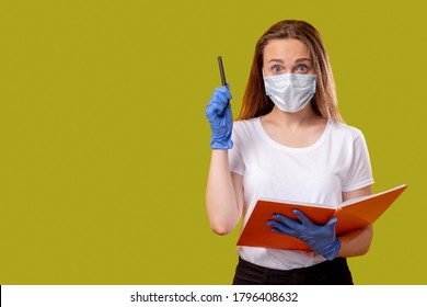 Quarantine class. Problem solution. Inspired female teacher in protective face mask gloves holding open book got idea pointing up with pen isolated on green copy space. Coronavirus hygiene measures.