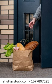 Quarantine contactless delivery banner with hand and delivered paper bag near the door. House entrance with delivered bag. Control Epidemic Prevention measures of coronavirus. Vertical banner