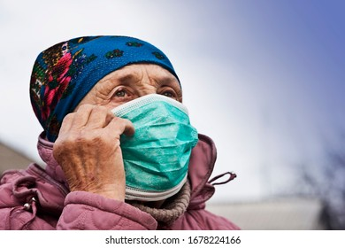 Quarantine coronavirus. Grandmother in a medical mask with a coronavirus. An old woman covers her face with a coronavirus. A coronavirus pandemic in the world. The state of emergency in connection wit
