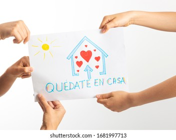 Quarantine at home during coronavirus pandemic in Spain. Family holding drawing picture with spanish words Quedate en casa - Stay at home. Social media campaign for coronavirus prevention
