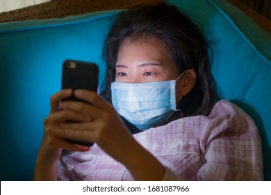 quarantine and home lockdown - young beautiful worried Asian Chinese woman in pajamas and surgical mask on couch searching online news on mobile phone scared about covid-19 virus outbreak