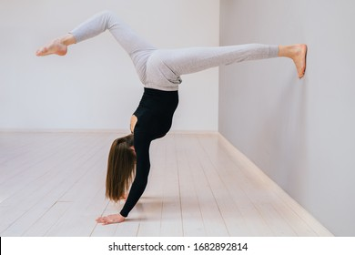 Quarantine at home. Sportive brunette fitness woman doing a handstand exercise at empty home or Lounge exercise. Conception of motherhood youth and energy. Side view