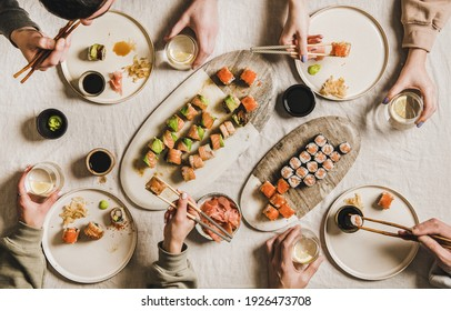 Quarantine Japanese sushi dinner from delivery or takeaway service at home. Flat-lay of people eating salmon, crab, prawn rolls variety, wasabi, ginger over light tablecloth background, top view