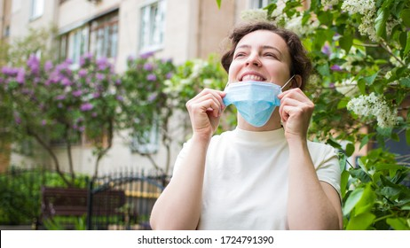 Quarantine is over concept. Smiling happy woman taking off medical protective mask outdoor. Freedom. Breathe deep. We are safe. We won. End of quarantine, isolation.