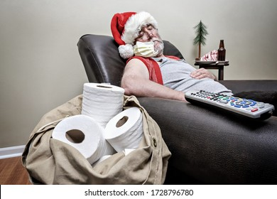 Quarantine Santa Claus sleeping in an recliner with face mask and pack full of toilet paper, focus on chair arm and remote and toilet paper