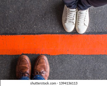 Quarantine, social distancing, separation, borders and barrier concept. Man and woman standing opposite of each other, divided by a red line.