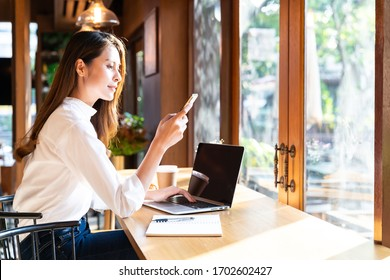 Quarantine Young asian woman wearing smart casual clothes work at home in living room using laptop and drinking hot coffee and croissant while city  lockdown for covid-19 corona virus pandemic.