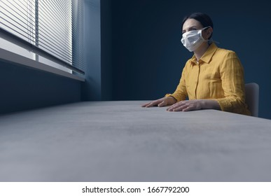 Quarantined lonely woman with covid-19 wearing a face mask and sitting at home alone in front of a window, virus outbreak emergency concept