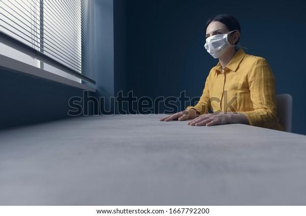 Mujer solitaria en cuarentena con covid-19 usando una máscara facial y sentada en casa sola frente a una ventana, concepto de emergencia de brotes de virus