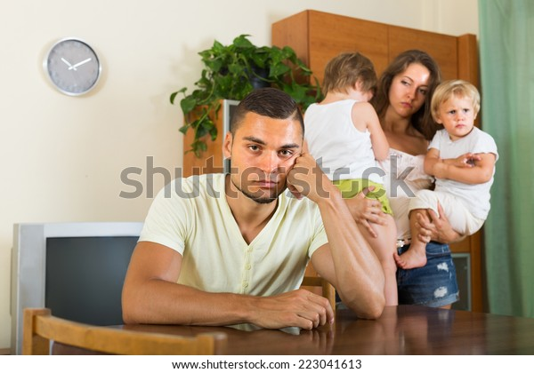 Quarrel between young parents with two little children at home