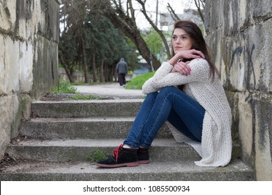 Quarrel and parting. Sad lonely girl sitting on the steps and her boyfriend go away into the distance.