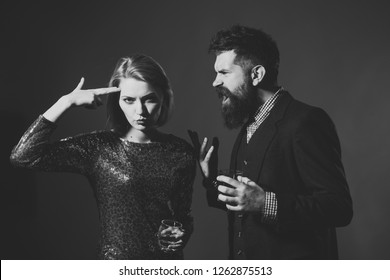 Quarrel and relations concept. Couple quarreled at corporate party. Woman fed up with quarrel in fancy dress and man screaming on blue background. Girl with gun gesture holds wineglass with wiskey.