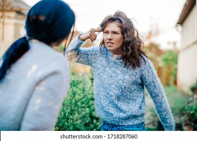 Quarrel two friends. Two women screaming at each other. Two young women argue. Family problem. Angry. Female. Nature background. Emotional. Emotion. Depression. People. Stress. Family photo.