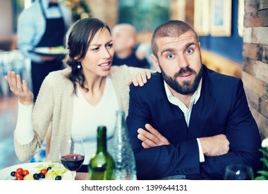 Quarreled visitors female and male at a restaurant on celebrate. Focus on man
