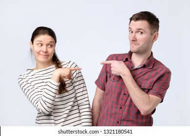Quarreling young couple man and woman accusing each other. It is not my fault. Coworker blaming each other.