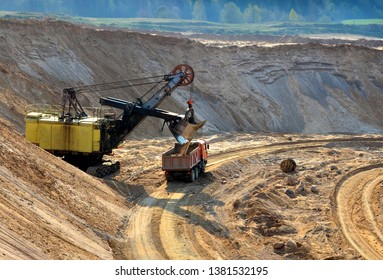 Quarry excavator loading sand or into dump truck at opencast. Excavation of mineral resources, the work of special mining equipment - Image
