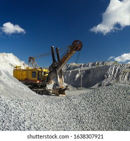 Quarry excavator stands against a background of fields of crushed stone and a dark blue sky, square image. Mining industry.