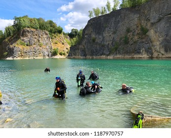 Quarry explored by scuba divers. Flooded quarry for adrenaline hobby. Diver site with fresh blue and clean water with divers. Divers in the blue quarry during summer. Floreffe, Belgium. 07/16/2018