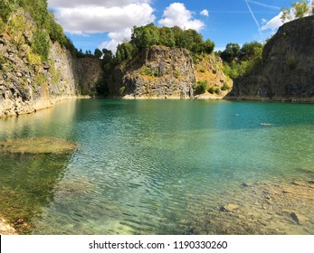 Quarry explored by scuba divers. Flooded quarry for adrenaline hobby. Diver site with fresh blue and clean crystal water with divers. Divers in the blue quarry during summer. Floreffe, Belgium.