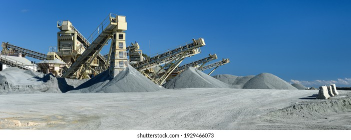 Quarry machines and piles of gravel over blue sky. Stone crushing and screening plant, panoramic view