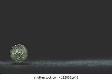 Quarter dollar coin spinning on dark background