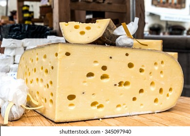 Quarter of Emmental cheese head on the market place.