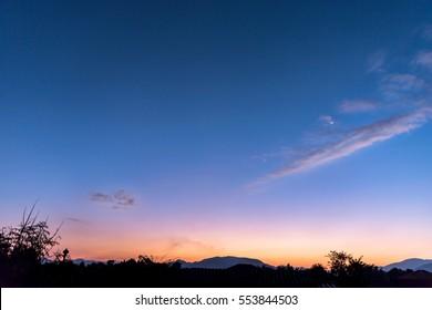 Quarter Moon rising behind silhoutted dark mountain