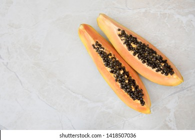 Quarter slices papaya on a marble surface with copy space.