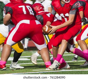 Quarterback turning to look for someone to hand off the ball to just after the snap during a high school football game