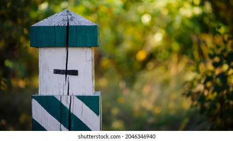 Quarterly pillar in the forest. A wooden pillar for a landmark in the forest. Forestry post. wood post with green stripes, blurred natural background. space for text