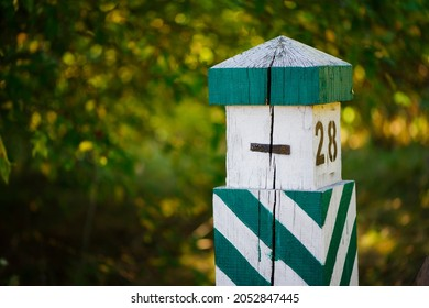 Quarterly pillar in the forest. A wooden pillar for a landmark in the forest. Forestry post. wood post with green stripes, blurred natural background. space for text. close-up