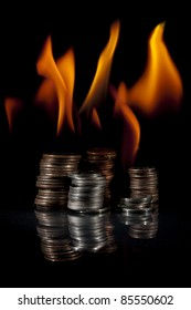 Quarters, dimes, nickels, and pennies in stacks on fire.