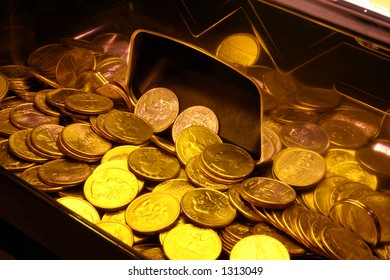 Quarters in a slot machine tray with yellow lighting