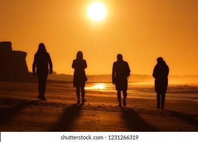 Quartet of four determined ladies walking toward the dawn of a new day. Four women on beach walk in Algarve coast Portugal.