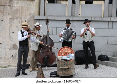 Quartet of Musicians playing musical instruments for tourists on the street in Prague